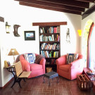 Our Arizona library with comfy chairs old school desk and hanging and recessed lighting. Also large exposed rafters along with brick flooring in a nice pattern